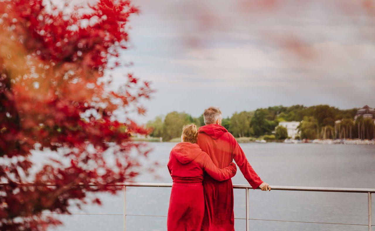Paar in roten Bademänteln genießt Ausblick über den herbstlichen Ruppiner See