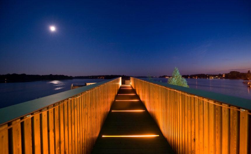 Beleuchteter Steg der Seesauna der Fontane Therme bei Nacht