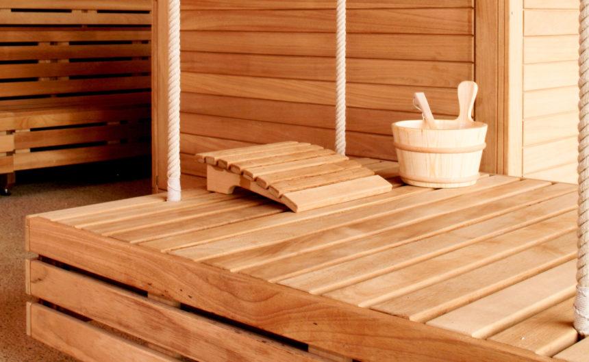 Hängende Holzliege mit Kopfstütze und Holzbottich in der Sauna der Therme Brandenburg