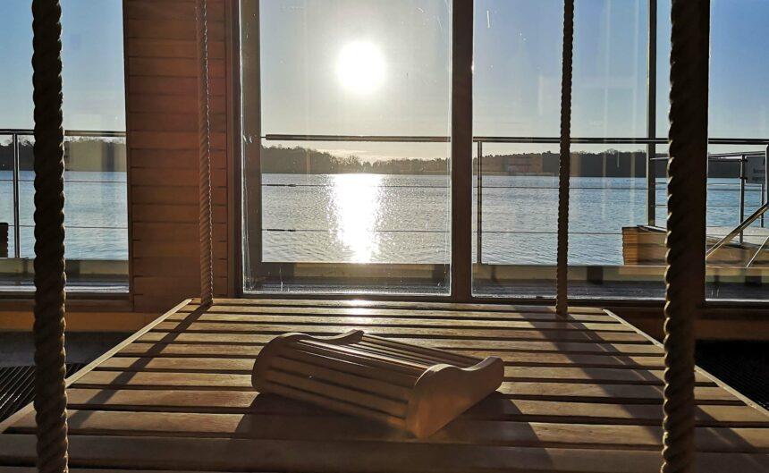 Detailaufnahme einer Holzliege im Ruhebereich der Therme mit Panoramablick auf den See