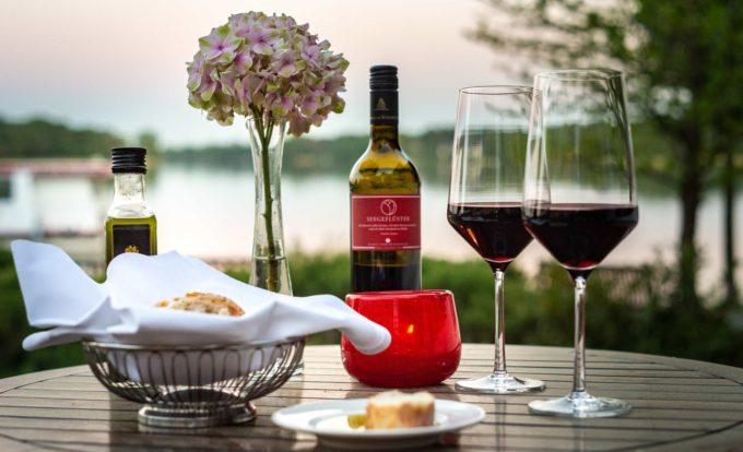 Ein Tisch im Garten des Resorts Mark Brandenburg mit Brotkorb und zwei Gläsern Rotwein