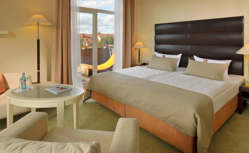 Kingsizebett im Komfortzimmer mit Balkon und Blick auf die Altstadt