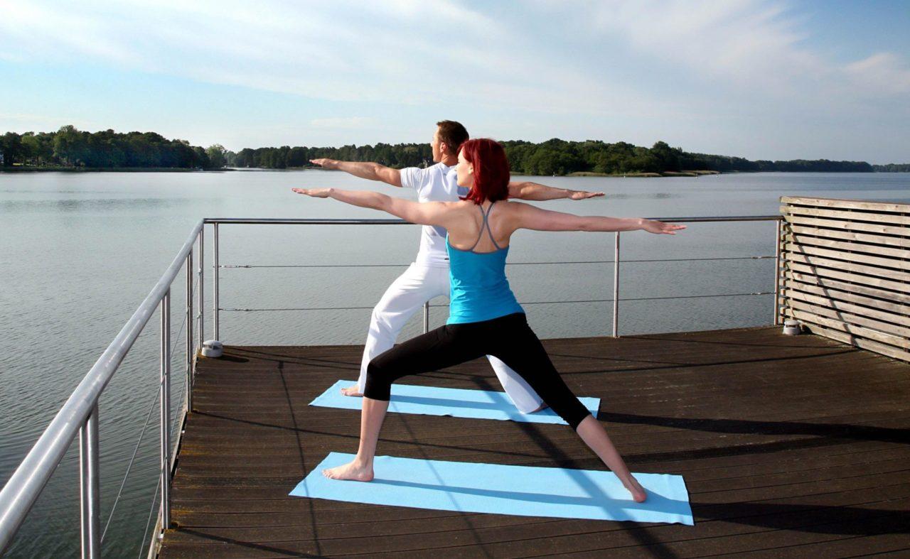 Paar beim Yoga auf der Dachterasse des Resorts Mark Brandenburg