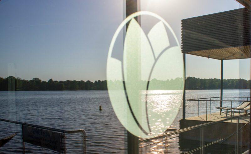 Blick durch die Glasscheibe der Therme Brandenburg auf den See