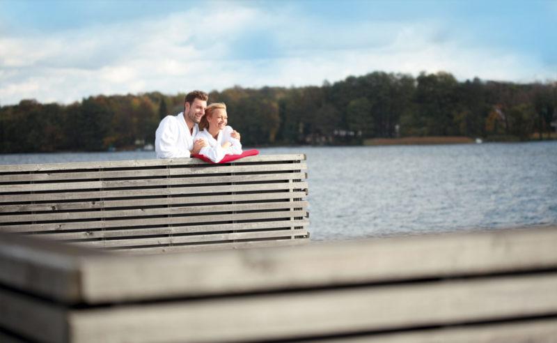 Ein Paar auf dem Sonnendeck mit Blick auf den See der Fontane Therme