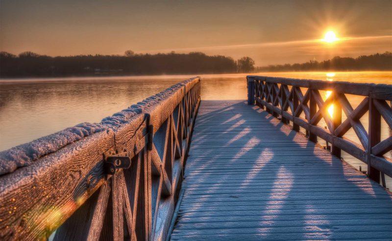 Schneebedeckter hölzerner Steg am Ruppiner See bei der Abendsonne