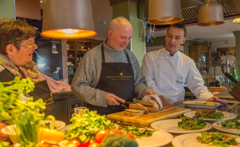 Küchenchef und Kochschüler beim Anrichten verschiedener Speisen im Restaurant in Neuruppin