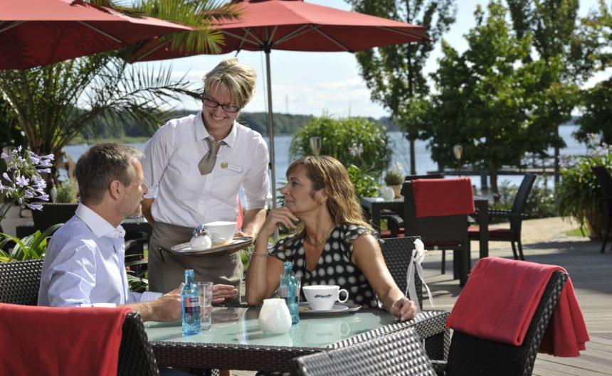 Ein Ehepaar sitzt auf der Terrasse des Restaurants Parzival im Resort Mark Brandenburg