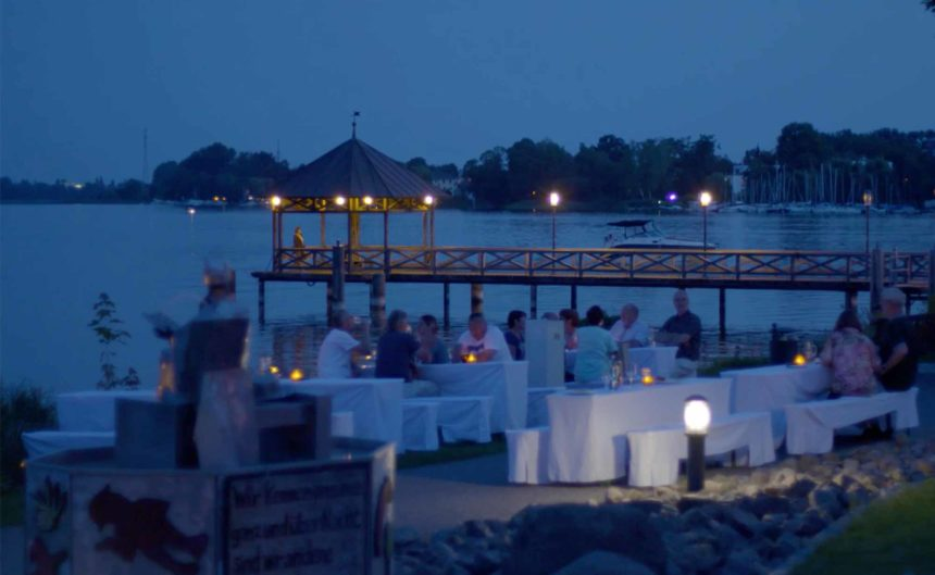 Gäste des Resorts Mark Brandenburg sitzen am Ruppiner See bei Dämmerung