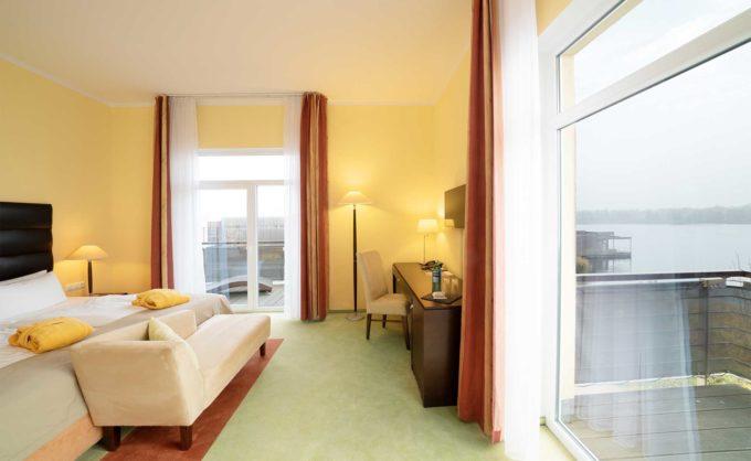 Schlafzimmer des Superior-Eckzimmers mit Balkon und Blick auf den See