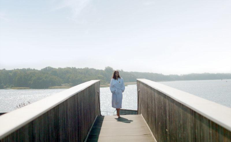 Ein Wellnessgast der Therme in Brandenburg auf dem Holzsteg zum See