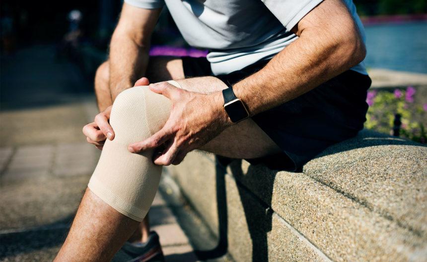 Mann sitzt auf Mauer und begutachtet sein Knie mit Bandage