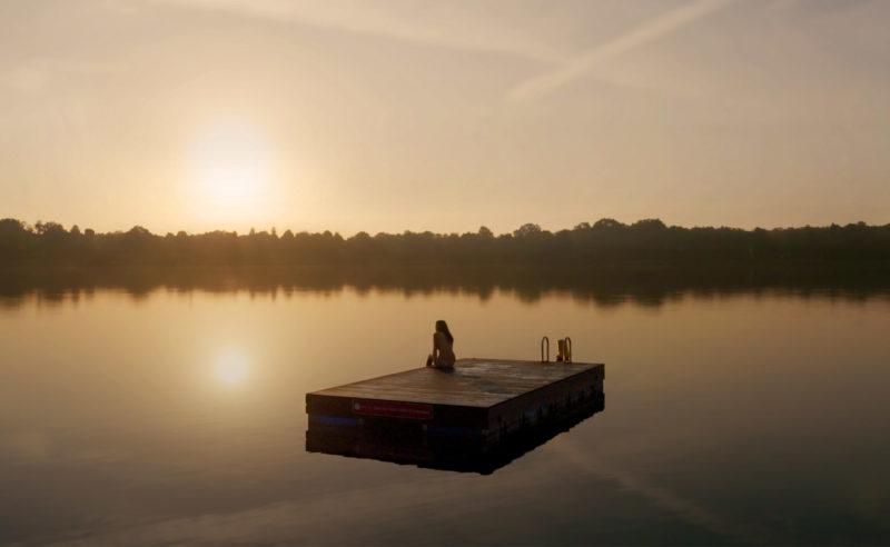 Eine Frau sitzt auf einem Floß und genießt den Sonnenuntergang