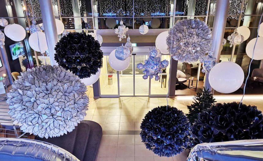 Kunstvolle Hängeleuchten in Form von großen Schneekristallen im Eingangsbereich des Hotels