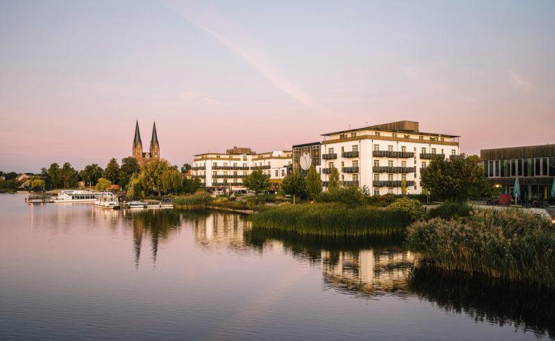 Das am Schilf gelegene Hotel Neuruppin mit zwei Kirchtürmen im Hintergrund