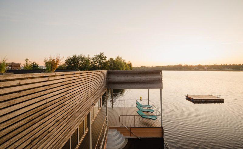 Außenansicht von der Dachterrasse der See Sauna mit Blick auf ein hölzernes Floß auf dem See