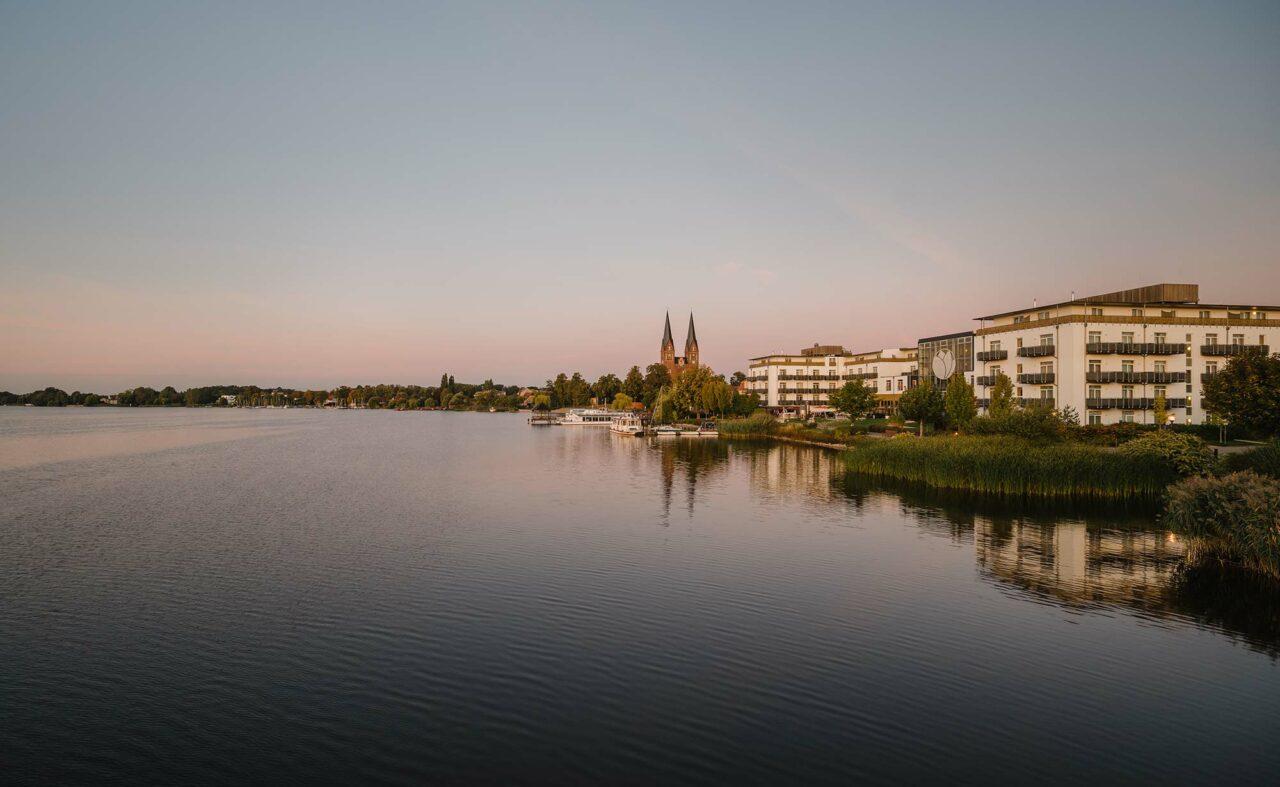 Außenaufnahme des Resort Mark Brandenburg aus See Perspektive mit Neuruppin im Hintergrund