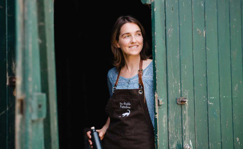 Frau mit Schürze steht angelehnt am Tor ihres Hofes und lächelt