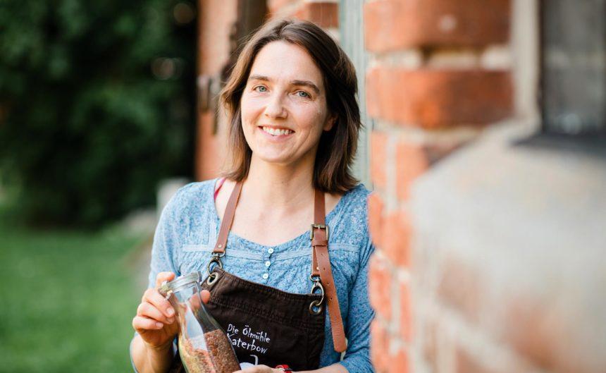 Mitarbeiterin der Öhlmühle hält ein Glas Körner in der Hand