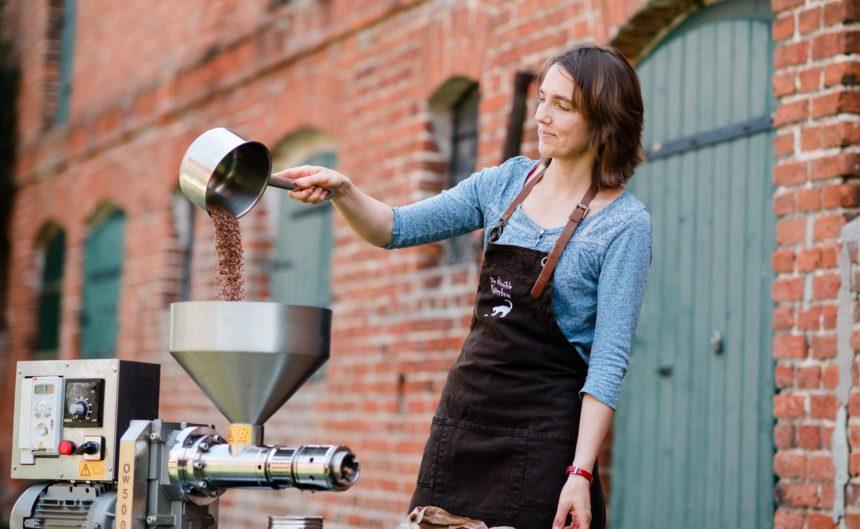 Frau mit Schürze schüttet Kaffeebohnen in einen Trichter zum zermahlen