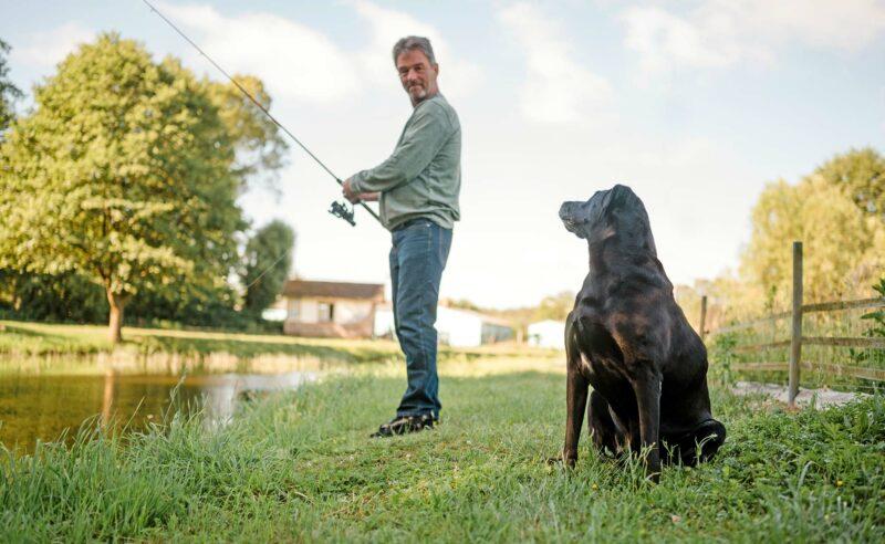 Partner Fischzucht beim Angeln mit seinem Hund