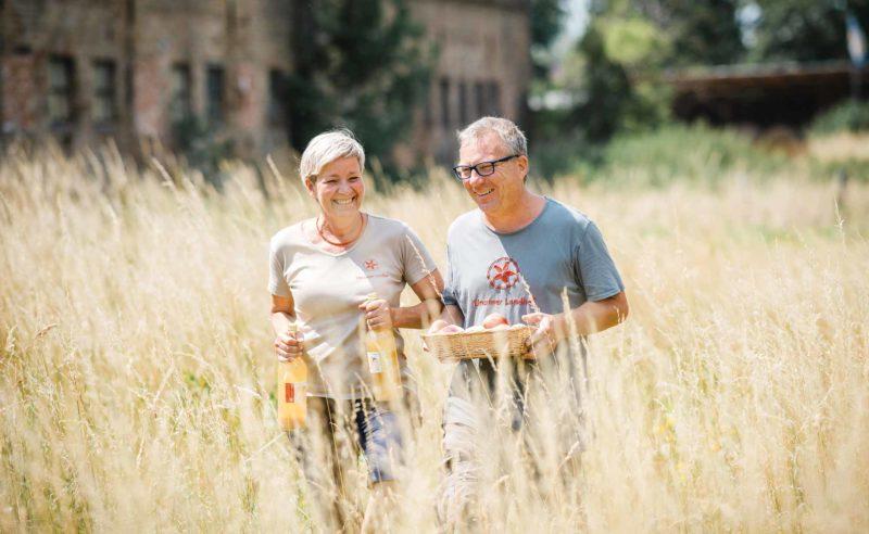 Mann und Frau Linum laufen über ein Feld und lächeln dabei