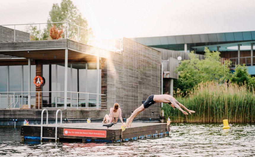 Besucher springt von einem Holzfloß im Ruppiner See