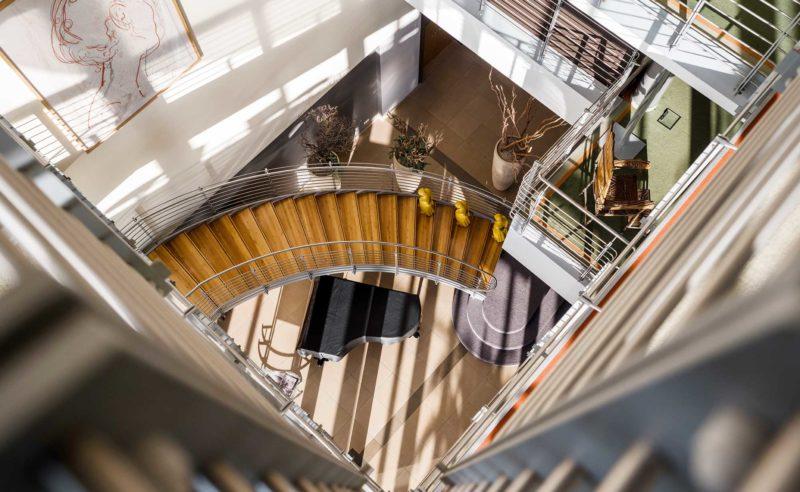 Blick vom Treppenhaus nach unten auf einen Klavierflügel im Hotel Neuruppin